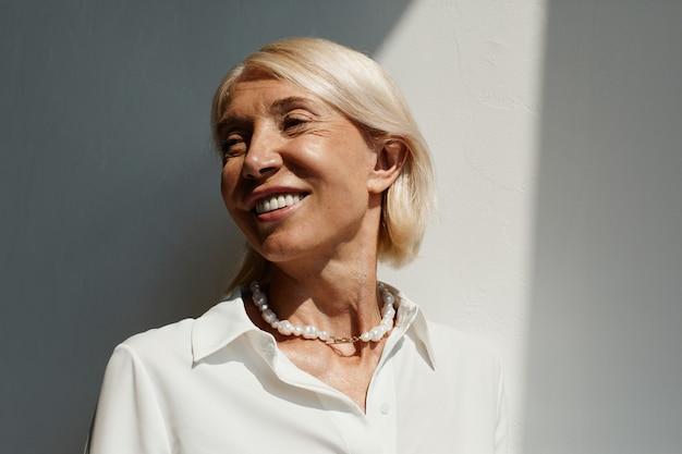 Минимальный портрет элегантной зрелой женщины, освещенной солнечным светом на белой стене и улыбающейся копии пространства