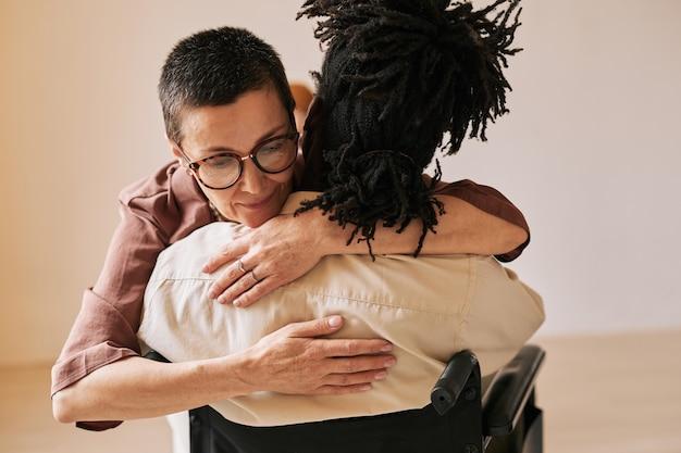 지원 그룹, 복사 공간에서 치료 세션 동안 휠체어에 남자를 껴안은 여성 심리학자의 최소한의 초상화