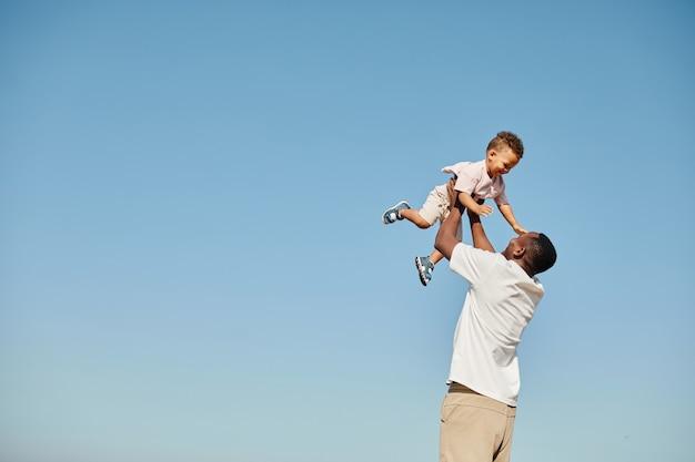 かわいい赤ちゃんと遊んで、青に対して彼を投げる幸せなアフリカ系アメリカ人の父の最小限の肖像画...