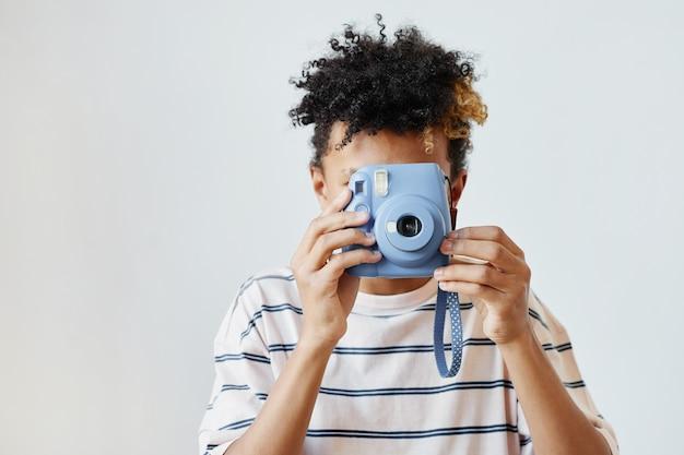 Минимальный портрет мальчика-подростка смешанной расы, держащего мгновенную камеру на белом фоне, копировальное пространство