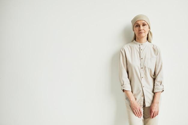 머리 스카프를 두르고 흰 벽 옆에 서서 카메라를 바라보는 수심에 찬 성숙한 여성의 최소한의 초상화, 공간 복사