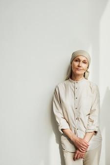 머리에 스카프를 두르고 햇빛 아래 흰 벽 옆에 서서 카메라를 바라보는 수심에 찬 성숙한 여성의 최소한의 초상화