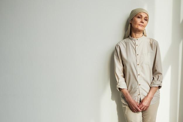 햇빛 아래 흰 벽 옆에 서 있는 동안 머리 스카프를 두른 수심에 찬 성숙한 여성의 최소한의 초상화, 복사 공간