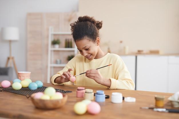 Минимальный портрет улыбающейся афро-американской девушки, расписывающей пасхальные яйца в пастельных тонах, наслаждаясь украшением дома своими руками, скопируйте пространство