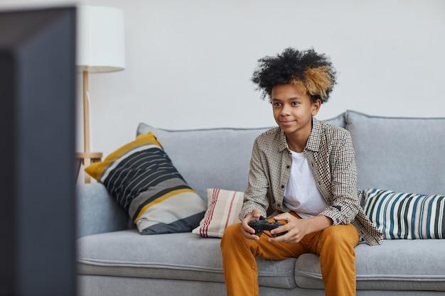 自宅でビデオゲームをプレイし、ゲームパッド、コピースペースを保持しながら幸せに笑っている10代のアフリカ系アメリカ人の少年の最小限の肖像画