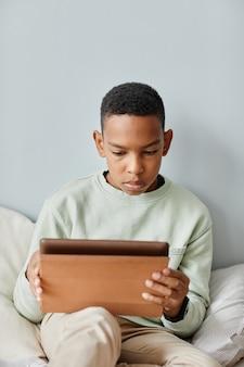 Минимальный портрет афроамериканского мальчика-подростка с помощью цифрового планшета, сидя на кровати у себя дома