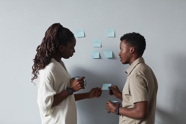 オフィスでプロジェクトを計画している間、壁にステッカーのメモを置く2人のアフリカ系アメリカ人の若者の最小限の肖像画、コピースペース