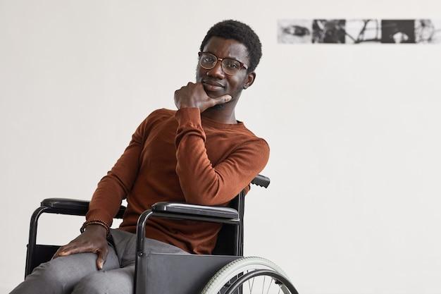 車椅子を使用し、現代アートギャラリーでポーズをとっている間、若いアフリカ系アメリカ人の男性の最小限の肖像画、