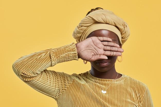 Минимальный портрет молодой афроамериканской женщины с головной повязкой и закрывающими глаза, стоя на ...