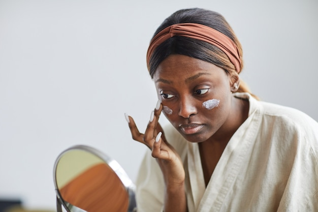 Minimal portrait of young african-american woman using face cream or moisturizer, skincare and beauty routine concept