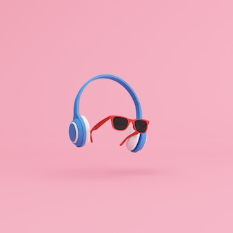 Minimal scene of sunglasses and headphone on pink background, music concept.