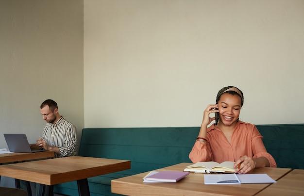 Минимальный снимок двух человек, работающих за столиками в кафе, сфокусирован на улыбающейся афро-американской бизнес-леди, говорящей по смартфону, копией пространства