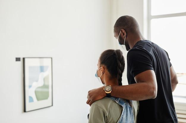 マスク、コピースペースを身に着けている現代アートギャラリーamdの絵画を見ているアフリカ系アメリカ人の家族の最小限の側面図