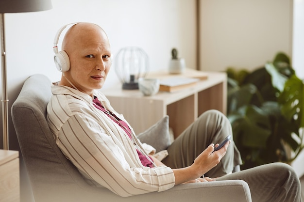 Minimal side view portrait of bald adult woman wearing headphones and looking at camera while listening to music via smartphone in cozy home interior, alopecia and cancer awareness, copy space