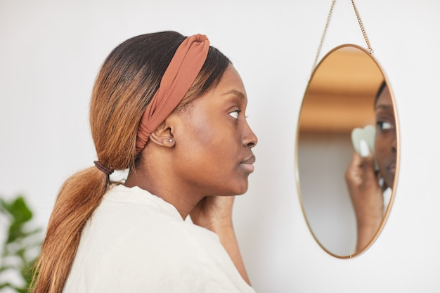 Minimal side view portrait of beautiful african-american woman enjoying skincare routine at home and looking at mirror, copy space