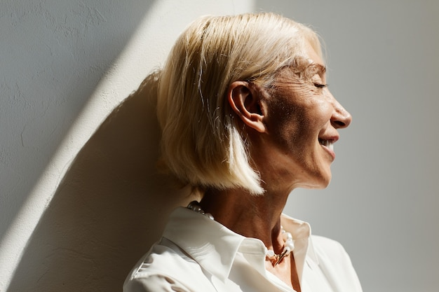 Minimal side view portrait of elegant mature woman lit by sunlight against white wall copy space