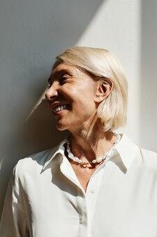 Минимальный вид сбоку портрет элегантной зрелой женщины, освещенной солнечным светом на белой стене