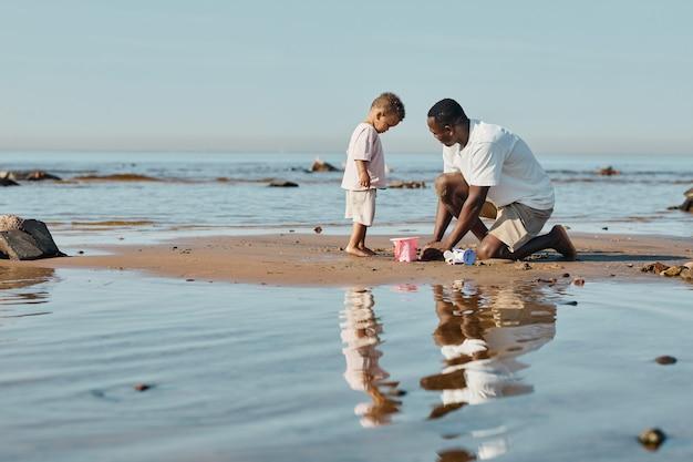ビーチで一緒に砂で遊んでいる若いアフリカ系アメリカ人の父と息子の最小限の側面図の肖像画...