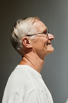 Minimal side view portrait of smiling senior man lit by sunlight against grey wall