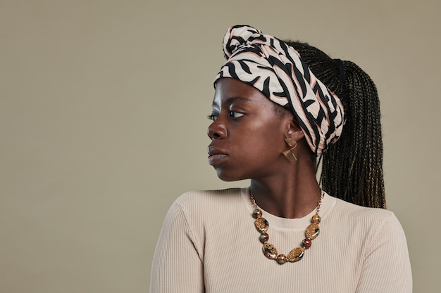 Minimal side view portrait of young africanamerican woman looking away while wearing ethnic accessor...