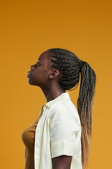 Minimal side view portrait of young africanamerican woman standing against yellow background in stud...