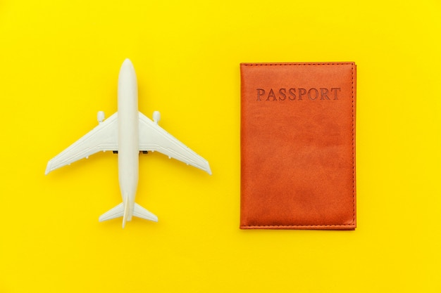 Minimal simple flat lay travel adventure trip concept with plane and passport on yellow trendy modern background