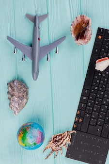 파란색 파스텔 현대적인 배경에 비행기 글로브와 조개껍데기가 있는 최소한의 단순한 평면입니다. 비행기 휴가 여름 주말 여행.
