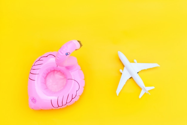 Minimal simple flat lay with plane and inflatable flamingo isolated on yellow background