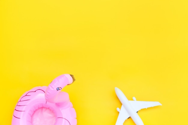 Minimal simple flat lay with plane and inflatable flamingo isolated on yellow