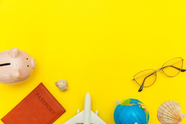 Minimal simple flat lay with plane passport sunglasses globe piggy bank and shell on yellow colourful trendy. tourist essentials