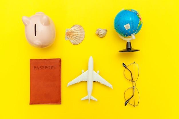 Minimal simple flat lay with plane passport sunglasses globe piggy bank sleeping eye mask and shell on yellow colourful trendy