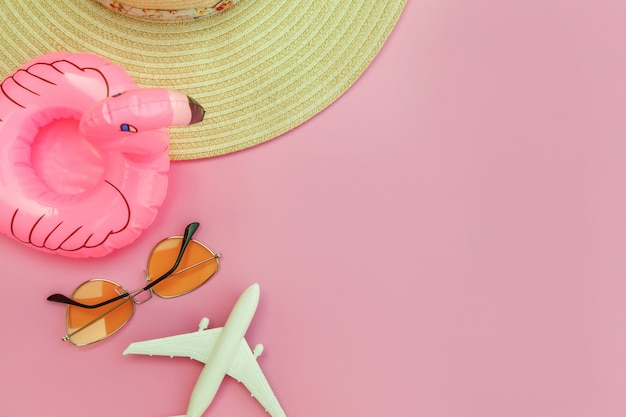 Minimal simple flat lay with plane sunglasses hat and inflatable flamingo isolated on pastel pink background