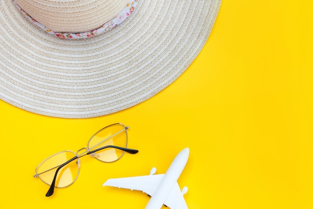Minimal simple flat lay with plane sunglasses and hat isolated on yellow