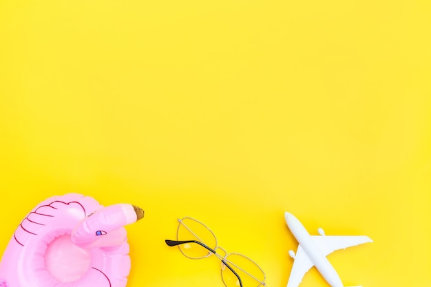 Minimal simple flat lay with plane sunglasses and inflatable flamingo isolated on yellow