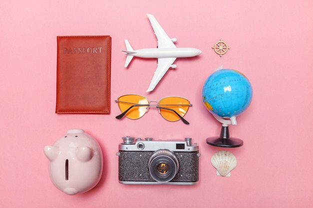Minimal simple flat lay with plane vintage camera passport sunglasses globe piggy bank and shell on pink pastel trendy modern
