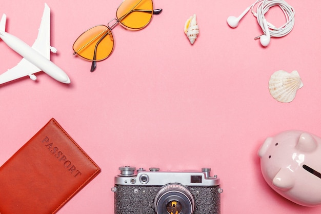 Minimal simple flat lay with plane vintage camera passport sunglasses piggy bank and shell on pink pastel trendy