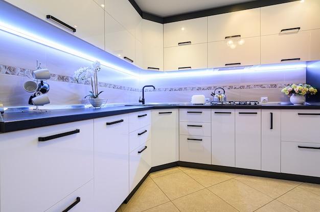 Минимальный простой белый большой современный интерьер кухни, крупным планом Premium Фотографии