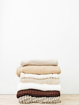 A minimal stack of warm beautiful feminine sweaters or pullovers lying on wooden table