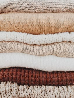 A minimal stack of warm beautiful feminine sweaters or pullovers with neutral beige, brown colors.