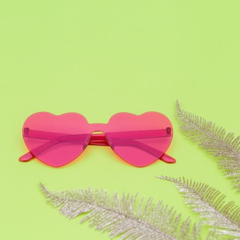 Minimal style fashion photography with heart shaped glasses and golden palm leaves on green paper background. modern pink sunglasses. trendly summer concept. copy space.