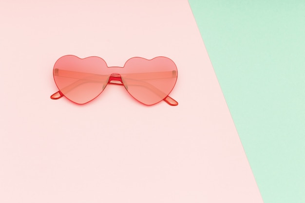 Minimal style fashion photography with heart shaped glasses on green and pink paper background. modern sunglasses. trendly summer concept. copy space.