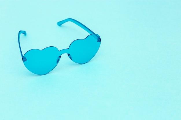 Минимальная фотография моды стиля с очками сердечной формы на синем. голубые современные солнцезащитные очки. модная летняя концепция. копировать пространство