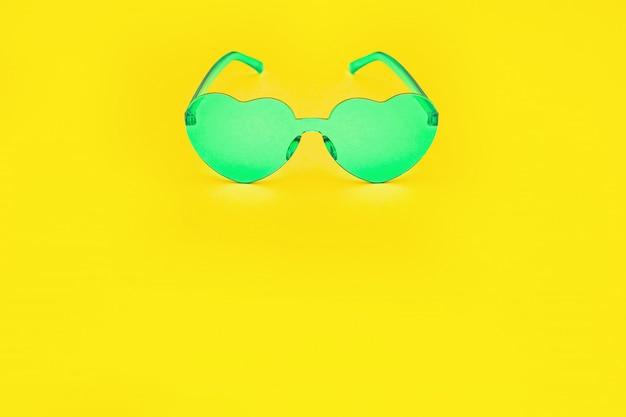 Минимальная фотография моды стиля с очками сердечной формы на ярко-желтой бумаге. зеленые современные солнцезащитные очки. модная летняя концепция. копировать пространство