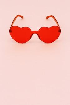 Минимальная фотография моды стиля с очками сердечной формы на бумажном фоне. красные современные солнцезащитные очки. модная летняя концепция. копировать пространство