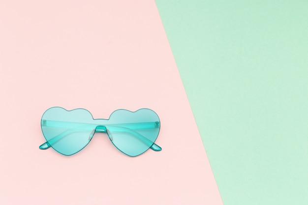 분홍색과 녹색 파스텔 컬러 배경에 심장 모양의 안경으로 최소한의 스타일 패션 사진.