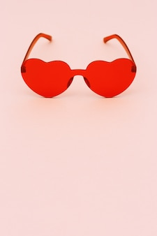 Minimal style fashion photography with heart shaped glasses on paper background. red modern sunglasses.  trendly summer concept. copy space.