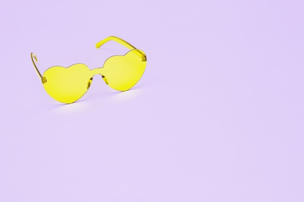 Minimal style fashion photography with heart shaped glasses on pink