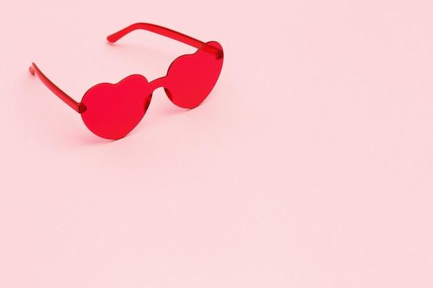 Минимальная фотография моды стиля с красными очками сердечной формы на розовом бумажном фоне. розовые современные солнцезащитные очки. модная летняя концепция. копировать пространство