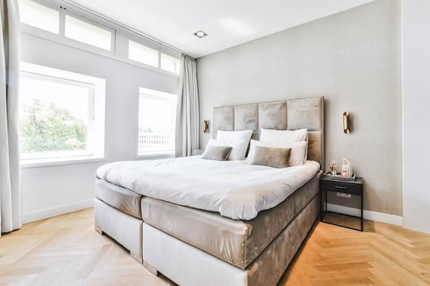 현대 아파트의 부드러운 침대와 쿠션이있는 침실의 미니멀 스타일 인테리어