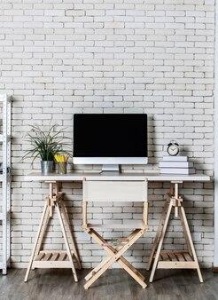 金属製の棚、コンピューターディレクターズチェア、レンガの壁を背景にした木製のテーブルを備えた、装飾の少ないオフィスコーナーを備えた最小限のスタイル。在宅勤務の概念。